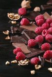 Variety of chopping chocolate with raspberries. Dark and milk chopping chocolate and chips shavings chopping chocolate with fresh raspberries heap and cracks Stock Photography