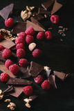 Variety of chopping chocolate with raspberries. Dark and milk chopping chocolate and chips shavings chopping chocolate with fresh raspberries heap and cracks Royalty Free Stock Photography