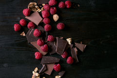 Variety of chopping chocolate with raspberries. Dark and milk chopping chocolate and chips shavings chopping chocolate with fresh raspberries heap and cracks Stock Images