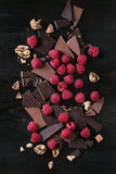 Variety of chopping chocolate with raspberries. Dark and milk chopping chocolate and chips shavings chopping chocolate with fresh raspberries heap and cracks Stock Image
