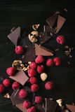 Variety of chopping chocolate with raspberries. Dark and milk chopping chocolate and chips shavings chopping chocolate with fresh raspberries heap and cracks Stock Photo