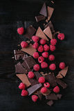 Variety of chopping chocolate with raspberries. Dark and milk chopping chocolate and chips shavings chopping chocolate with fresh raspberries heap over black Stock Photography