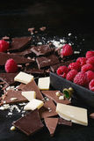 Variety of chopping chocolate with raspberries. Variety of dark, milk and white chopping chocolate with fresh raspberries in black wood box over black burnt Royalty Free Stock Photo