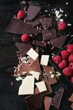 Variety of chopping chocolate with raspberries. Variety of dark, milk and white chopping chocolate with fresh raspberries in black wood box over black burnt Royalty Free Stock Image