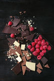 Variety of chopping chocolate with raspberries. Variety of dark, milk and white chopping chocolate with fresh raspberries in black wood box over black burnt Royalty Free Stock Images
