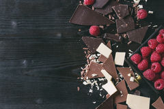 Variety of chopping chocolate with raspberries. Variety of dark, milk and white chopping chocolate with fresh raspberries in black wood box over black burnt Royalty Free Stock Photos