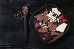 Variety of chopping chocolate with raspberries. Variety of dark, milk and white chopping chocolate on old plate and spoon with fresh raspberries in black wood Royalty Free Stock Images