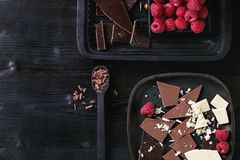 Variety of chopping chocolate with raspberries. Variety of dark, milk and white chopping chocolate on old plate and spoon with fresh raspberries in black wood Royalty Free Stock Photography