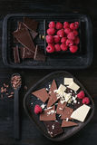 Variety of chopping chocolate with raspberries. Variety of dark, milk and white chopping chocolate on old plate and spoon with fresh raspberries in black wood Stock Photos
