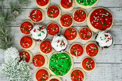 Variety of Christmas holiday treats with chocolate cupcakes and buttercream iced sugar cookies - top view flatlay on wood