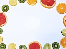 Fruit story. Variety of citrus and kiwi on white background. The view from the top. Variety of citrus and kiwis arranged in a circle on a white background. The royalty free stock image