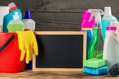Variety cleaning product with small empty chalk board. On wooden table, close up stock photography