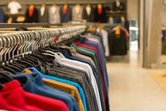 Variety of clothes hanging on rack in boutique Stock Images