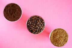 A variety of coffee - three types in one picture: roasted beans, ground and instant granulated. In round glass bowls on a pink. Background. Diagonal. View from stock photos