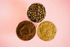 Variety of coffee - three types in one picture: roasted beans, soluble granulated and ground. In round glass bowls on a pink. Background. Vintage processing royalty free stock photography