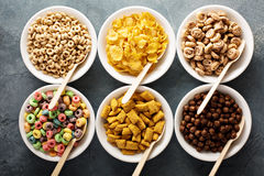 Variety of cold cereals in white bowls with spoons. Variety of cold cereals in white bowls with wooden spoons, quick breakfast for kids Royalty Free Stock Images