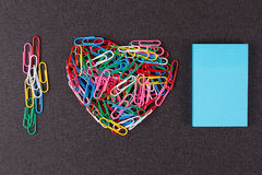 Variety of color paper clips arranged in heart shape Stock Photography