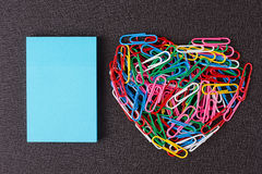 Variety of color paper clips arranged in heart shape Stock Image
