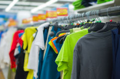Variety of color T-shirts on stands in supermarket Royalty Free Stock Image