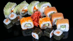 A variety of colored sushi rolls sets and ginger on the mirror surface on a black background. Japanese cuisine in studio. A variety of colored sushi rolls sets stock video