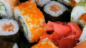 A variety of colored sushi rolls sets and ginger on the mirror surface on a black background. Japanese cuisine in studio. A variety of colored sushi rolls sets stock footage