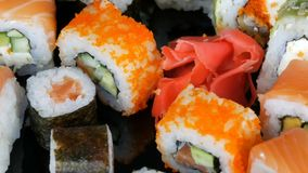 A variety of colored sushi rolls sets and ginger rotate on the mirror surface on a black background. Japanese cuisine in. The studio stock footage