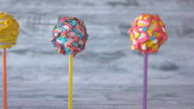 Variety of colorful cake pops. Assortment of sweet balls on sticks with colorful icing. Delicious snack for kids stock footage
