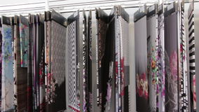 A variety of colorful fabric samples on display. Automated industrial sewing weaving knitting embroidery loom machine in textile cotton industry production stock footage