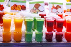 A variety of colorful, fruity drinks on ice in a Barcelona, Spain market stock photography