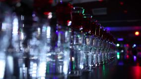 Variety of colorful green blue yellow red and white beautiful alcohol sweet shooters shots cocktail fresh beverage in. Small glasses standing in row on bar stock footage