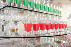 Variety of colorful green and red alcohol shots in small glasses standing in row on a glass stand Royalty Free Stock Images