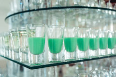 Variety of colorful green and red alcohol shots in small glasses standing in row on a glass stand Stock Photo