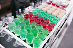 Variety of colorful green red and white beautiful alcohol sweet shooters shots cocktail fresh beverage in small glasses Stock Images