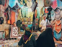 Variety of colorful rugs, tapestries and lady bags for sale at the Vakil Bazaar. Shiraz, Iran. stock images