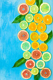 Variety of colorful sliced citrus fruits oranges, grapefruits, lemons, limes with green leaves on blue background, styled composit Stock Photography