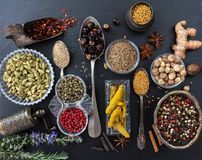 Variety of colorful spices and herbs on black stone background, top view royalty free stock photo