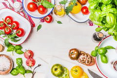 Variety on colorful tomatoes with flavoring and salad ingredients in enamelled bowls for tasty summer cooking on light wooden back. Ground, top view, frame Stock Photo