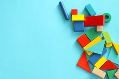 Colorful toy blocks flat lay on blue background. Variety of colorful toy blocks in pile on blue background, flat lay view with room for text Stock Photos