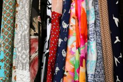 Row of Colorful Women`s Dress Fabric. A variety of colorful women`s clothing and dress of different fabrics, materials and patterns are hanging in the closet stock photos