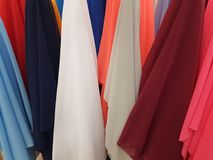 Variety of fabrics in different colors displayed in a shop. Variety of colors, textured background, abstract multicolored, material for clothing and decoration Stock Images