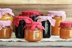 Variety of Covered Homemade Fruit Jams. Variety of homemade jams and preserves covered with checkered and red cloth against a rustic background. Extreme shallow stock photography