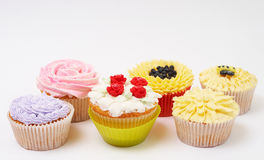 Variety of cupcakes with decorative techniques. Variety of vanilla cupcakes with various decorations on white background Stock Image