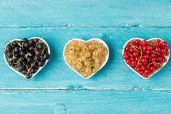 Variety of currant berries black, red and white in heart shape bowls on blue wooden background. summer food concept. Flat lay. top view royalty free stock photos