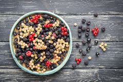 A variety of currant berries yellow and red,black and red raspberries, on a rustic ceramic dish, wooden old table. The view from t royalty free stock images