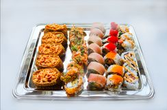 Variety of cut delicious sushi served on a silver platter on a white surface - selective focus stock photography