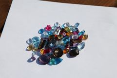 Cut gemstones piled on paper. Variety of cut precious gemstones piled on paper sparkling in light. The gemstones will end up in a variety of jewelry. Carved stock photo
