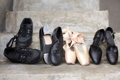 Variety of Dance Shoes. Closeup of a pair of jazz shoes, tap shoes, ballet pointe shoes, and character shoes representing a variety of dance classes in one image royalty free stock images