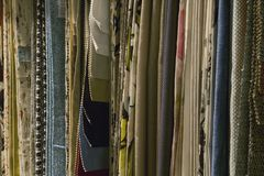 Variety of decorative fabric samples. Different home fabric samples hanged in a decoration store Stock Images