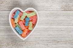 Sweet and Sour Candy Sugar Junk Food. Variety of different color sweet and sour candy or sugar junk food in a heart shaped bowl with copy space royalty free stock photo