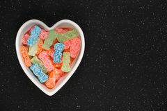 Sweet and Sour Candy Sugar Junk Food. Variety of different color sweet and sour candy or sugar junk food in a heart shaped bowl stock image
